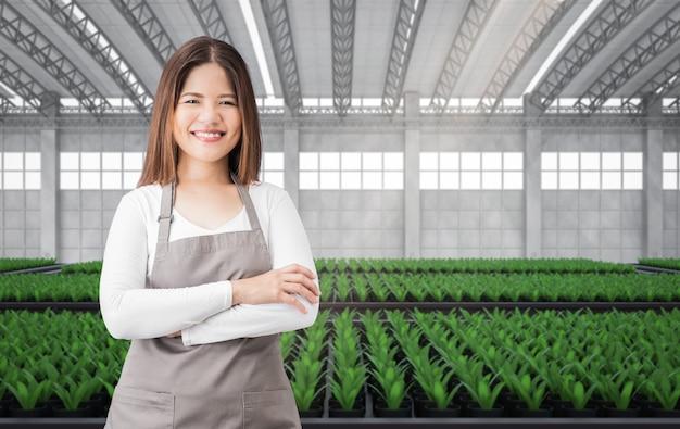 緑の家や植物でいっぱいの温室で幸せな女性の庭師