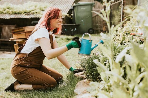 幸せな女性の庭師の水やり植物
