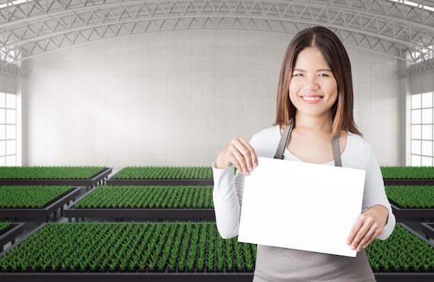 植物でいっぱいの温室または温室で空白のメモを持つ幸せな女性の庭師