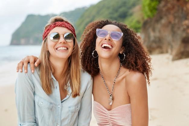 Felice coppia gay femminile di diverse nazionalità, si abbracciano, ridono allegramente e contro la scogliera e il paesaggio marino. la famiglia dello stesso sesso ha un resort estivo insieme.