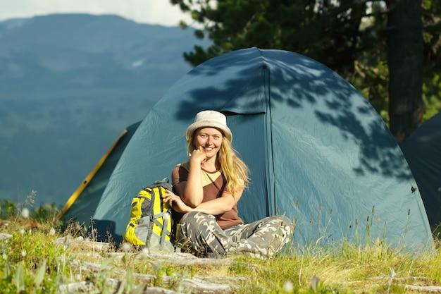 Felice femmina escursionista davanti alla tenda del campo