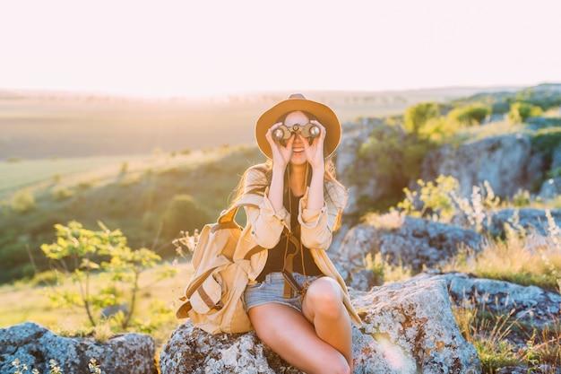 Happy female hiker looking through binocular