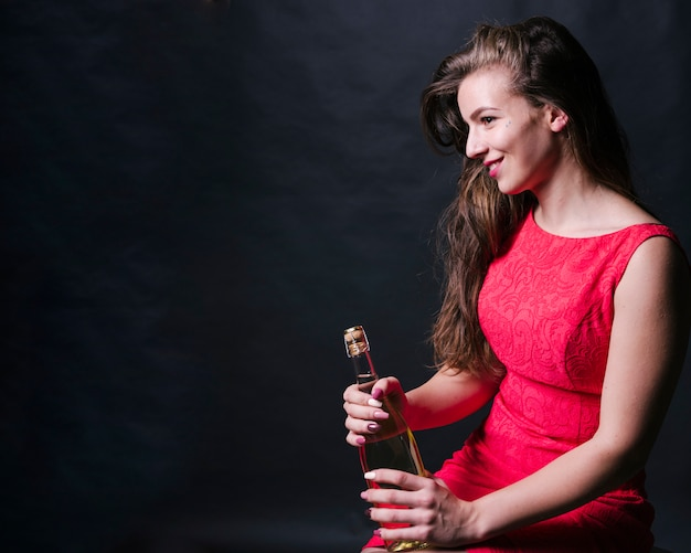 Happy female holding bottle of champagne