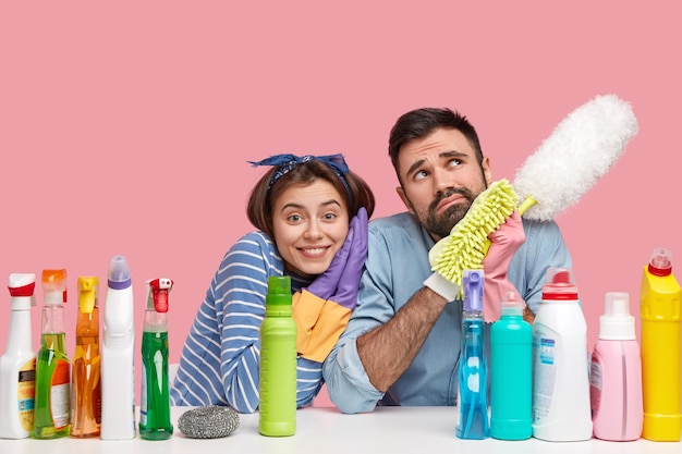 Happy female housekeeper leans at shoulder of thoughtful husband, cleans house together, do housekeeping, surrounded with cleaning detergents, hold mop, dust room have little rest after tired work.