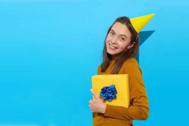노란색 종이에 싸서 서있는 동안 카메라를보고 선물 상자를 들고 파티 모자에 행복한 여성