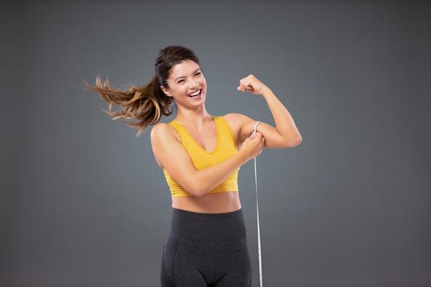 Счастливая женщина в спортивной одежде перед серой стеной, измеряя ее мышцы руки с лентой.