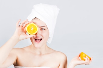 Happy female in towel with oranges at face