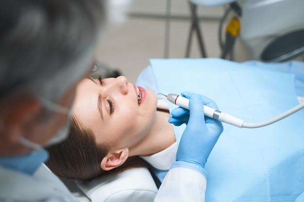 Счастливая женщина проводит время в стоматологическом кресле, пока мужчина-специалист помогает ей и осматривает инструменты