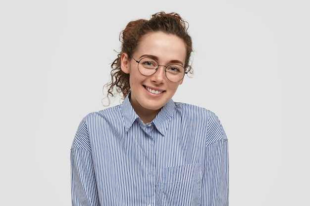Giornalista femminile felice felice di avere una conversazione piacevole con lo sconosciuto, ha un sorriso gentile, denti bianchi perfetti, pelle lentigginosa, vestito con una camicia a righe, isolato su un muro bianco bianco. concetto di positività