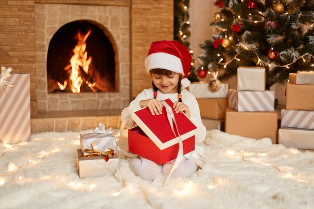 Happy female kid opening present box on new year eve, wearing white sweater and santa claus hat, sitting on floor near christmas tree, present boxes and fireplace.