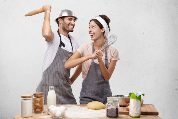 Happy female and male foolish at kitchen, fight with whisk and rolling pin, have glad expressions