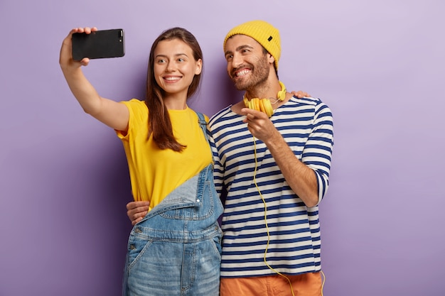 Happy female and male teenagers take selfie on smartphone, smile and embrace, cuddle each other, dressed in fashionable clothes, stand against purple wall, point at display, photograph themself