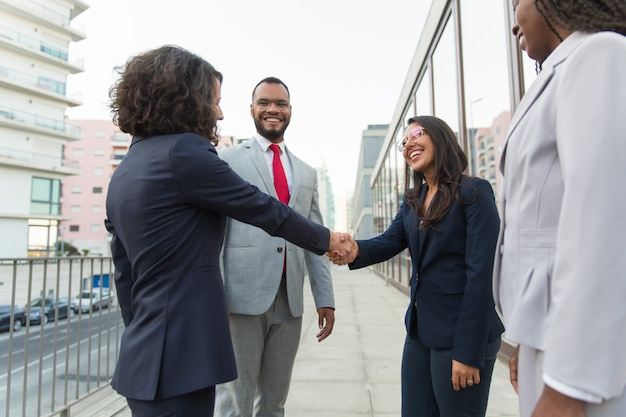 Happy female manager welcoming partners outside