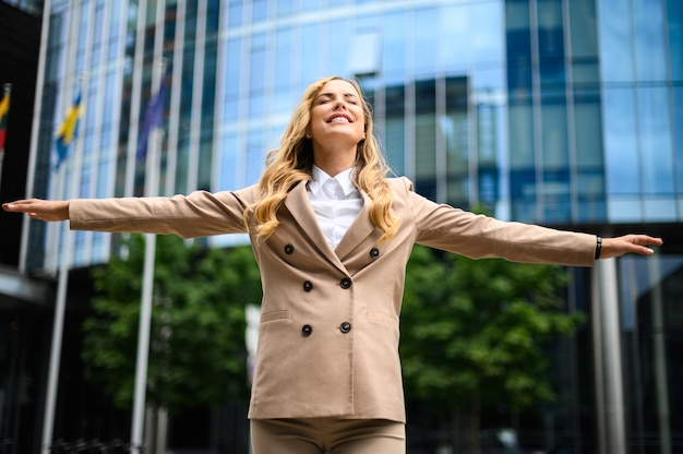 Happy female manager with open arms in sign of freedom and success
