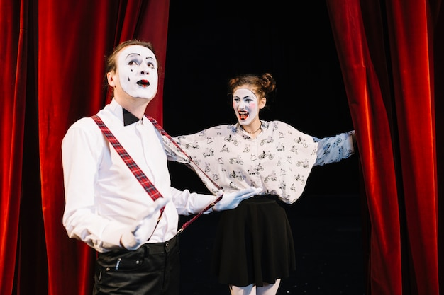 Happy female mime looking at male mime holding suspender on stage