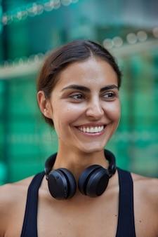Счастливая девушка-модель радостно выглядит где-то с белыми зубами, здоровая кожа наслаждается отдыхом, одетая в повседневную одежду, использует современные стереонаушники для прослушивания размытых песен