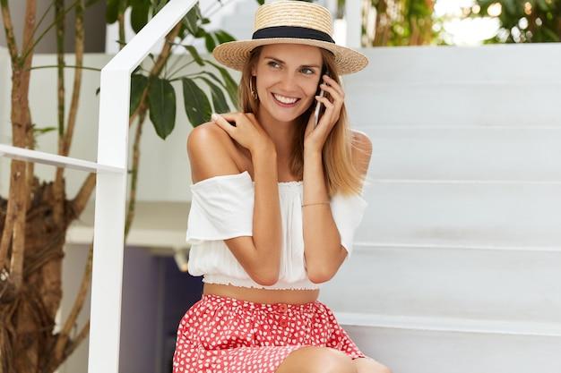幸せな女性モデルは白い階段でポーズし、スタイリッシュな夏の帽子、ブラウス、スカートを着用し、誰かと快適な電話で会話し、暑い国で休んでおり、前向きで忘れられない印象を共有しています