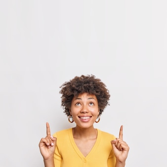Happy female model with curly hair points up at top advertisement smiles broadly shows special offer or item on discount wears yellow jumper stands against white wall