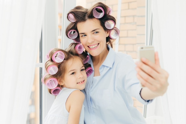 Happy female mother and her small child with curlers on head, pose for making selfie, use modern smart phone