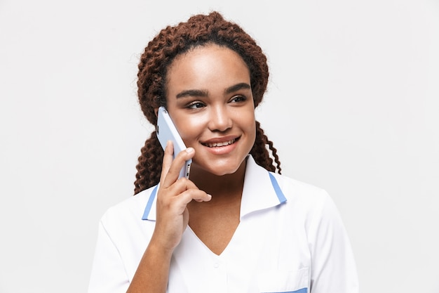 Happy female nurse wearing medical coat holding and talking on cellphone isolated against white wall