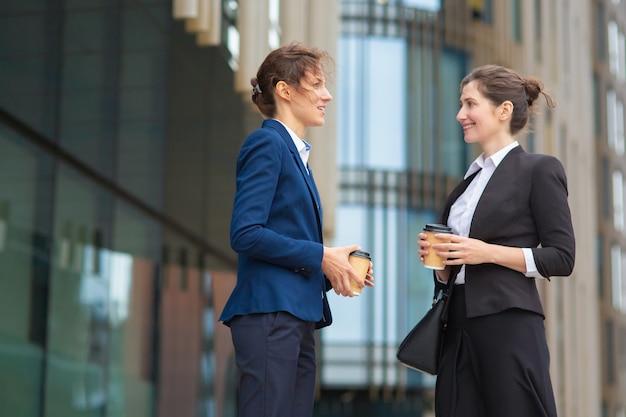 Счастливые друзья-женщины в офисе с чашками кофе на вынос, встречающимися на открытом воздухе, беседами, обсуждениями проекта или чатами. вид сбоку. концепция перерыва в работе