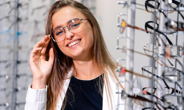 Happy female optometrist, optician is standing near set of glasses