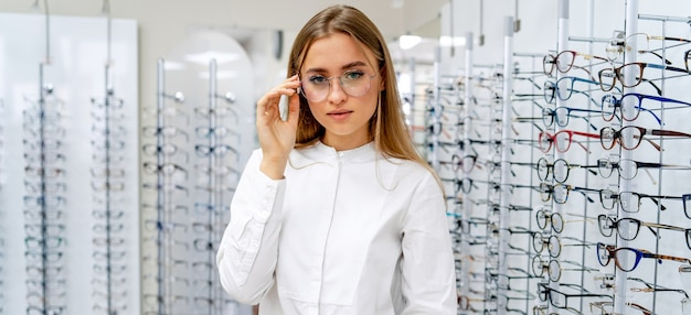 Happy female optometrist, optician is standing with many glasses  in optical shop.