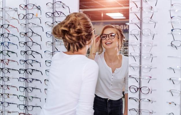 幸せな女性の検眼医、眼鏡技師が立っています