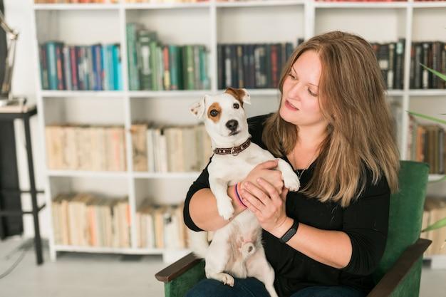 ジャックラッセルテリア犬の幸せな女性の所有者は、本棚の背景に立って、ペットの世話をする責任を感じています。人と動物との関係
