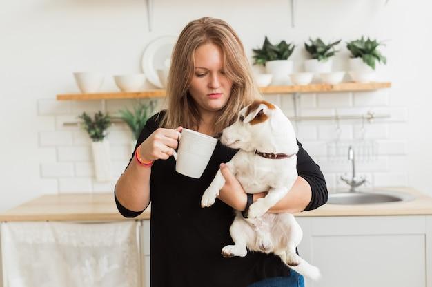 ジャックラッセルテリア犬の幸せな女性の所有者は、キッチンの背景に立って、ペットの世話をする責任を感じています。人と動物との関係