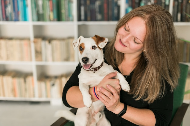 ジャックラッセルテリア犬の幸せな女性の所有者は、ペットの立っていることを気にする責任を感じています