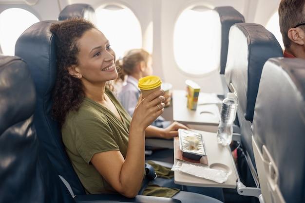 Счастливый женский пассажир пьет кофе и улыбается, пока женский бортпроводник обслуживает обед на борту. путешествия, услуги, транспорт, концепция самолета
