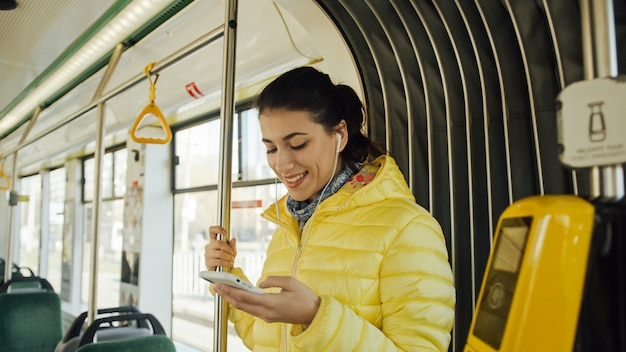 Happy female passenger listening to music on a smartphone in public transportation.