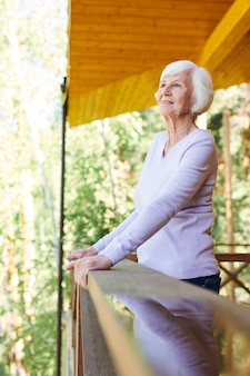 여름 날에 그녀의 시골집의 나무 난간에 의해 서 흰색 캐주얼 풀오버에 행복 여성 연금