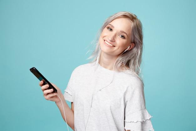 Счастливый женский человек с наушниками и телефоном, слушая музыку в студии.