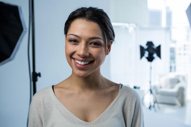 Happy female photographer standing in studio