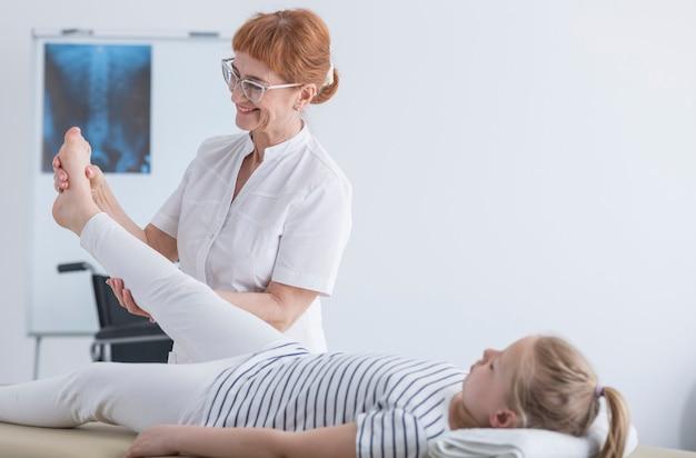 Счастливый женский физиотерапевт, работающий с пациентом в детской клинике сколиоза