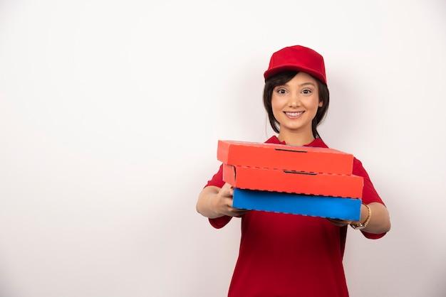 Lavoratore di consegna pizza femminile felice che dà tre cartoni di pizza.