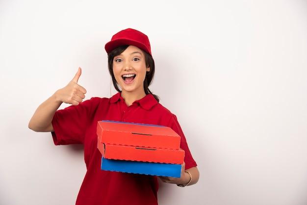 ピザの3つの段ボールで立っている幸せな女性のピザ配達労働者。