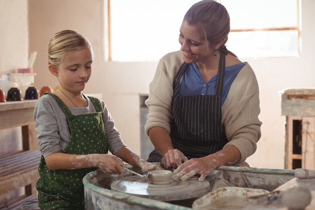 Happy female potter assisting girl