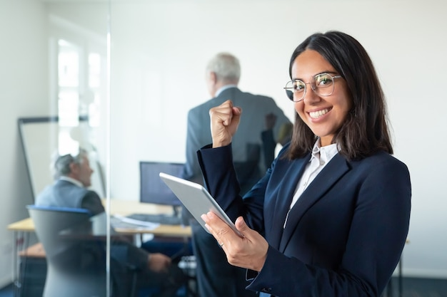 Happy female professional in glasses and suit holding tablet and making winner gesture while two businessmen working behind glass wall. copy space. communication concept