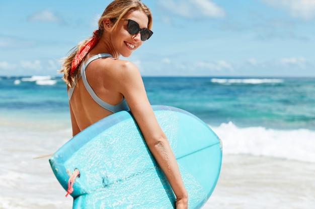 幸せな女性のプロのサーファーは、トレンディなサングラスと青い水着を着て、サーフィンボードを運んで、サーフィンに最適なスポットを持っている、青い海の景色に立ち向かいます。アクティブなライフスタイル
