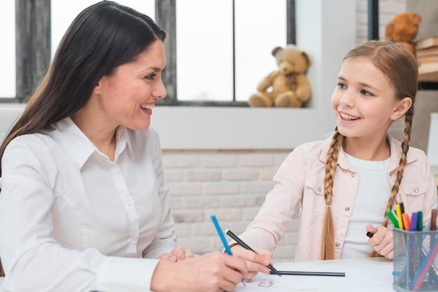 幸せな女性心理学者と女の子の色鉛筆とフェルトペンを紙に描く
