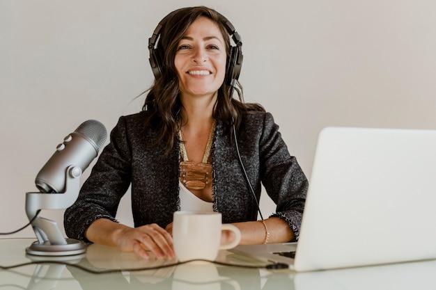 스튜디오에서 라이브로 방송하는 행복한 여성 라디오 진행자
