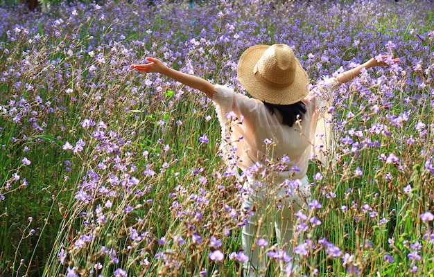 Happy female raising up her arms enjoy morning sunlight among the beautiful purple flower field
