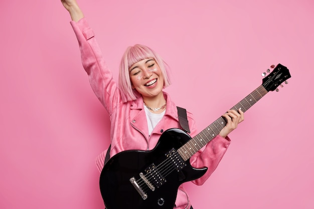 Happy female rockstar smiles happily keeps arm raised up plays electric guitar wears stylish jacket demonstrates her talents on stage