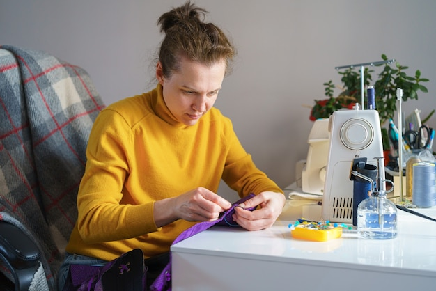 Happy female seamstress looking at future garment while working remotely at her workspace at home