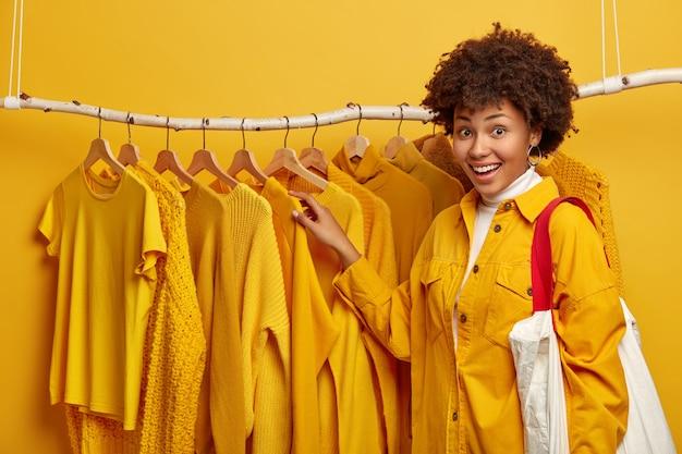 행복한 여성 쇼핑 중독자가 옷장에있는 옷걸이에 옷을 선택하고 밝은 재킷을 입고 가방을 들고 매력적인 미소를지었습니다.