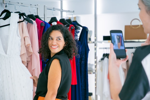 一緒に洋服店で買い物を楽しんだり、ドレスに触れたり、ポーズをとったり、携帯電話で写真を撮ったりする幸せな女性の買い物客。消費主義またはショッピングの概念