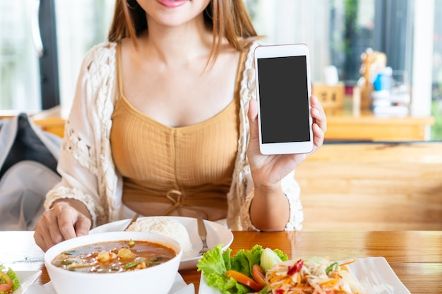 Happy female sitting in the restaurant and showing empty copy space smartphone